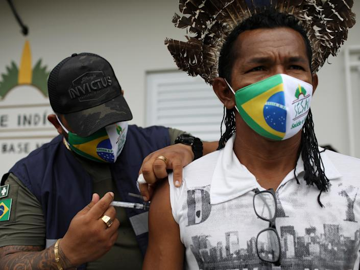 Healthcare workers have reportedly been confronted by crowds armed with bows and arrows while attempting to deliver the Covid-19 vaccine to an indigenous community in Brazil (Bruno Kelly/Reuters)