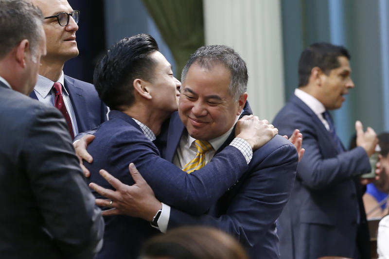 Assemblyman Phil Ting, D-San Francisco, right, chairman of the Assembly Budget Committee is congratulated by fellow Bay Area Democrat, Assemblyman Evan Low, left, after the Assembly approved the state budget in Sacramento, Calif., Thursday, June 13, 2019. Both houses of the Legislature approved the $214.8 billion state budget that spends more on health care and education, bolsters the state's top firefighting agency and boost state reserves. (AP Photo/Rich Pedroncelli)