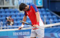 <p>TOKYO, JAPAN - JULY 31: Novak Djokovic of Team Serbia reacts at match point to be defeated by Pablo Carreno Busta of Team Spain during the Men's Singles Bronze Medal Match on day eight of the Tokyo 2020 Olympic Games at Ariake Tennis Park on July 31, 2021 in Tokyo, Japan. (Photo by Amin Mohammad Jamali/Getty Images)</p>
