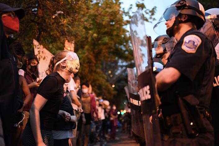 Protesters confront a row of police officers at Lafayette square, in front of the White House, in Washington, DC on June 22, 2020.