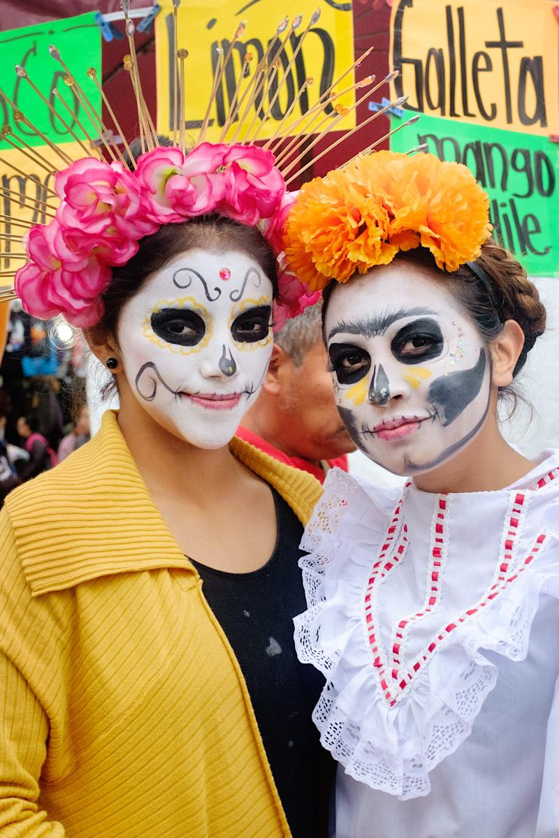 Young women from Xochimilco pose with their La Catrina face paint.