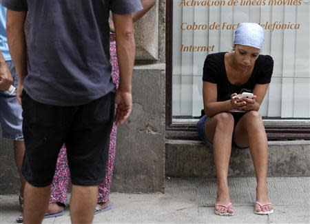 A woman uses her mobile phone on a street in Havana