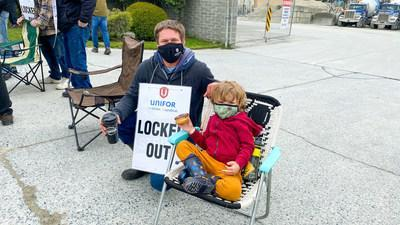 """Photo of worker wearing a """"Locked Out"""" sign posing with a young child at a picket line in Victoria, B.C. (CNW Group/Unifor)"""