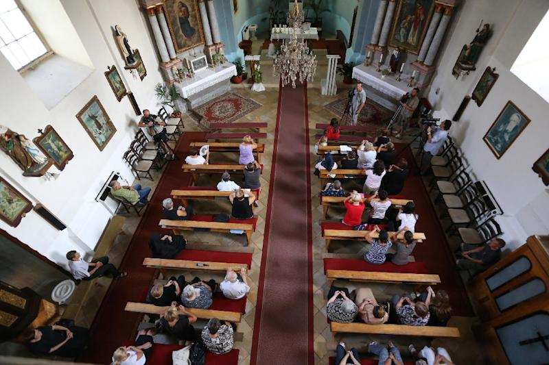People pray in a local church in Vrpolje on August 12, 2015, after hearing the news that the Islamic State group claims to have beheaded Croatian hostage Tomislav Salopek (AFP Photo/)