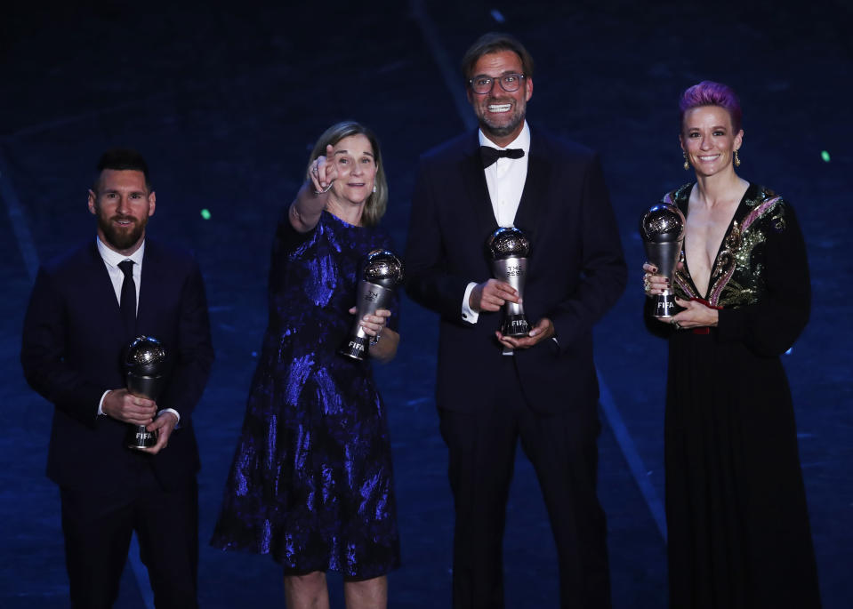 Argentinian Barcelona player Lionel Messi , United States women's World Cup winning coach Jill Ellis, Liverpool manager Juergen Klopp and United States forward Megan Rapinoe pose after they received the Best FIFA coach award , best FIFA men's , Women's player award during the Best FIFA soccer awards ceremony, in Milan's La Scala theater, northern Italy, Monday, Sept. 23, 2019. (AP Photo/Antonio Calanni)