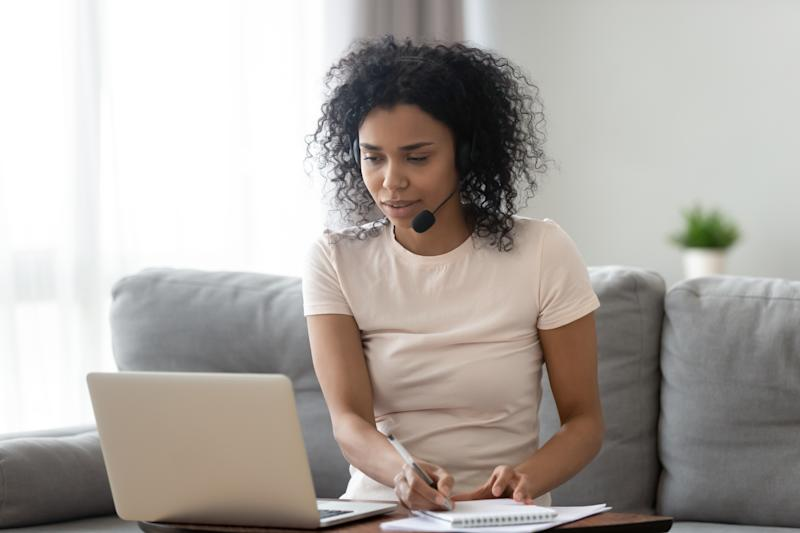 Young african woman wearing wireless headset looking at laptop making notes, focused black girl student teacher watching webinar online training talking by video conference call, e learning concept