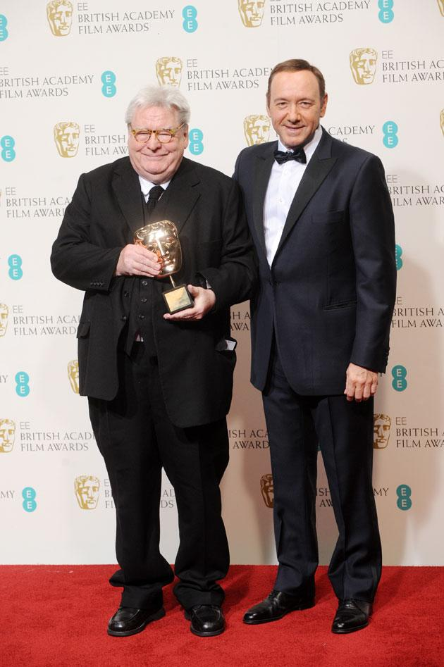 Sir Alan Parker, winner of the Fellowship award, poses in the press room with presenter Kevin Spacey at the EE British Academy Film Awards at The Royal Opera House on February 10, 2013 in London, England. (Photo by Stuart Wilson/Getty Images)