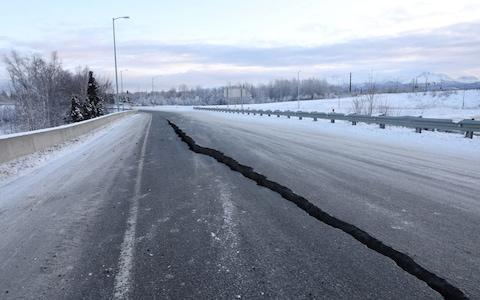 A crack which opened up along a roadway near the airport is seen after an earthquake in Anchorage - Credit: Reuters