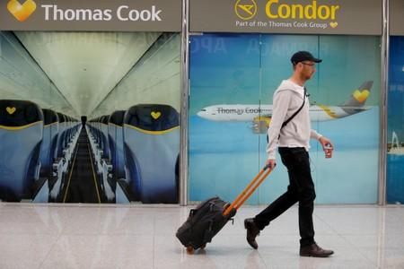 A passenger passes Thomas Cook banners at Mallorca Airport as an announcement is expected on the tour operator