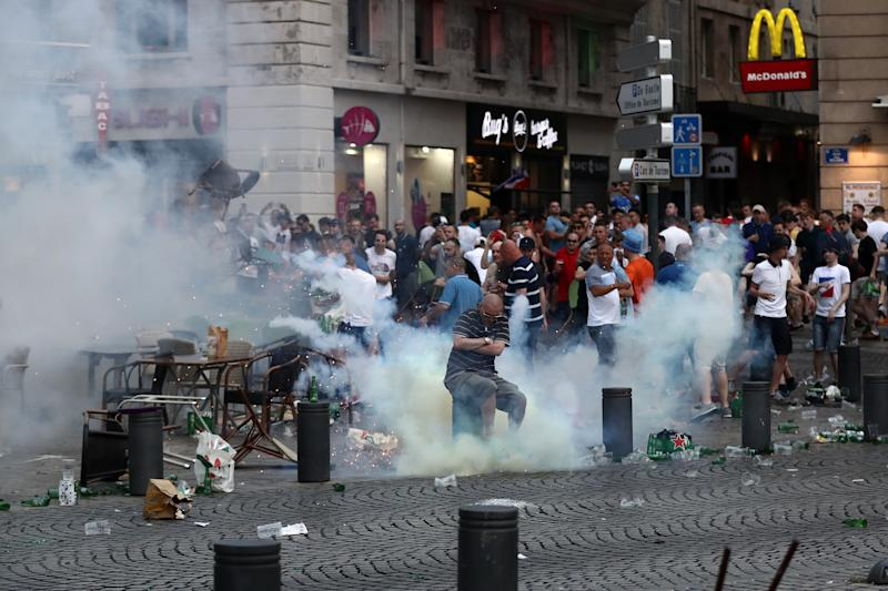 MARSEILLE, FRANCE - JUNE 10: A tear gas canister explodes under a football fan as England fans clash with police in Marseille on June 10, 2016 in Marseille, France. Football fans from around Europe have descended on France for the UEFA Euro 2016 football tournament. (Photo by Carl Court/Getty Images)