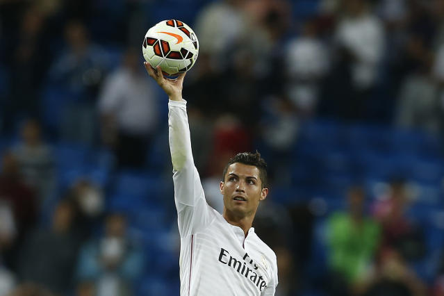 FILE - In this Sept. 23, 2014 file photo Real's Cristiano Ronaldo holds the ball as he celebrates his four goals during a Spanish La Liga soccer match between Real Madrid and Elche at the Santiago Bernabeu stadium in Madrid, Spain. (AP Photo/Andres Kudacki, files)