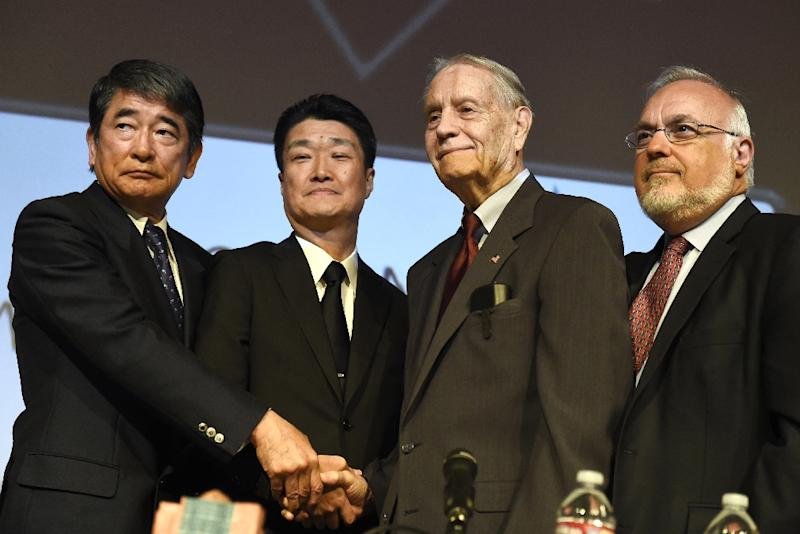 American World War II prisoner of war James Murphy (2nd right) shakes hands with Mitsubishi Materials executives in Los Angeles on July 19, 2015 (AFP Photo/Robyn Beck)