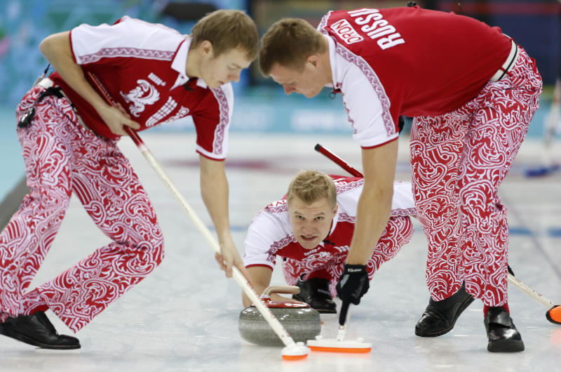 Russia's skip Alexey Stukalskiy, center, delivers the rock to sweepers Evgeny Arkhipov, left, and Petr Dron during men's curling competition against Great Britain at the 2014 Winter Olympics, Monday, Feb. 10, 2014, in Sochi, Russia. (AP Photo/Robert F. Bukaty)