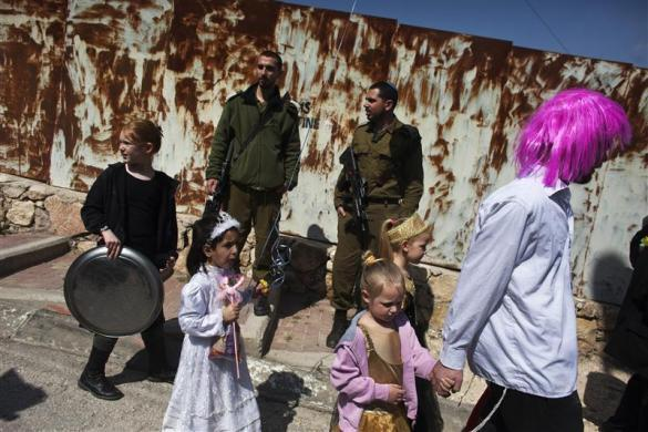 A Jewish settler (R) wearing a wig walks with children past Israeli soldiers standing guard in the West Bank city of Hebron March 8 2012, as they take part in a parade for the Jewish holiday of Purim.