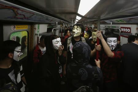 Pro-democracy protesters wearing Guy Fawkes masks take a subway train to a protest site occupied by them as part of the Occupy Central civil disobedience movement in Hong Kong November 5, 2014, the day marking Guy Fawkes Night. REUTERS/Bobby Yip