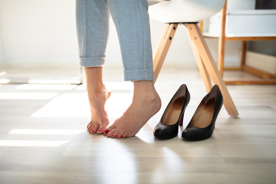 Close-up Of A Woman's Leg Near High Heels On Hardwood Floor