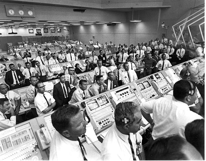 Kennedy Space Center control room team members rise from their consoles to watch the liftoff of the Apollo 11 mission on July 16, 1969. (Photo: NASA/AFP/Getty Images)