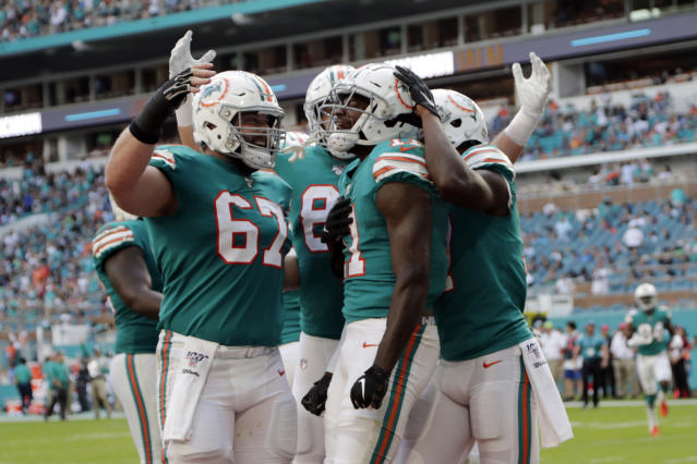 Miami Dolphins center Daniel Kilgore (67) congratulates wide receiver DeVante Parker (11) after Parker scored a touchdown during the second half at an NFL football game against the Philadelphia Eagles, Sunday, Dec. 1, 2019, in Miami Gardens, Fla. (AP Photo/Lynne Sladky)