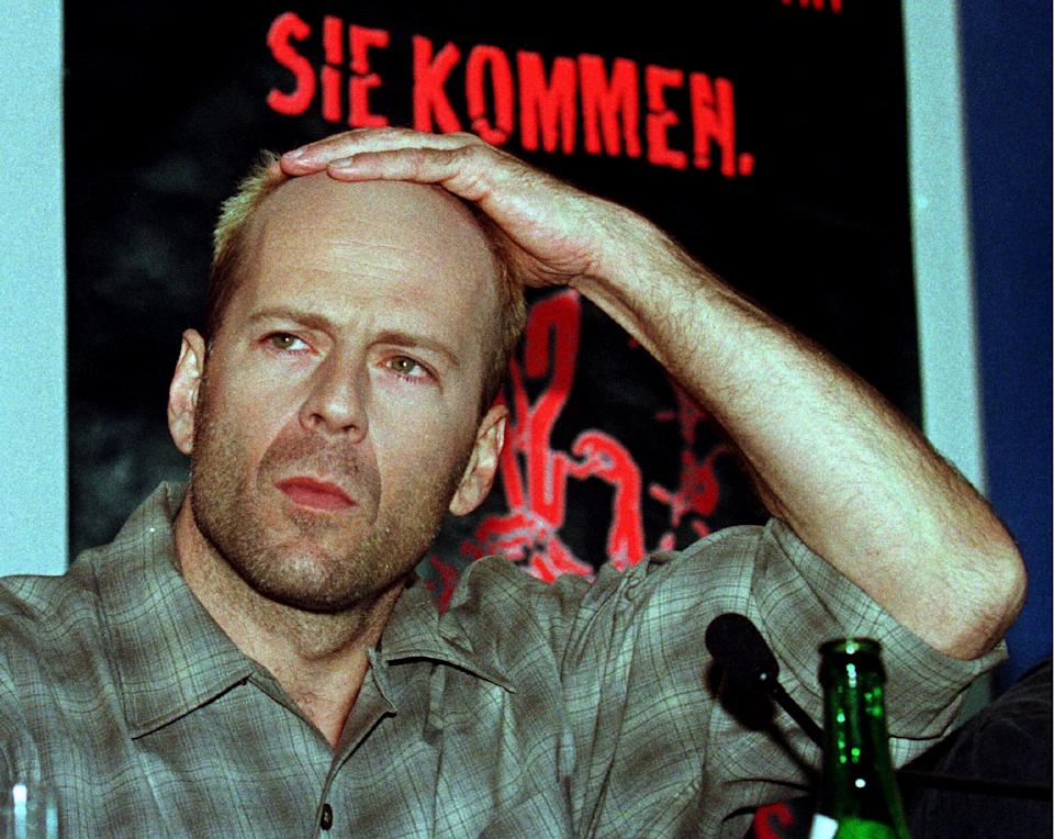 """US actor Bruce Willis scratches his head during the press conference where he presents his new movie """"12 Monkeys"""" in Berlin on February 24. The film was entered to the competition of the 46th International Film Festival which will end on February 26. GERMANY FILM"""