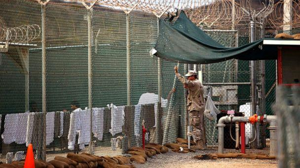 PHOTO: A U.S. Army guard leans on a fence talking to a Guantanamo detainee, inside the open yard at Camp 4 detention center, at the U.S. Naval Base, in Guantanamo Bay, Cuba, Jan. 21, 2009. (AFP via Getty Images, FILE)
