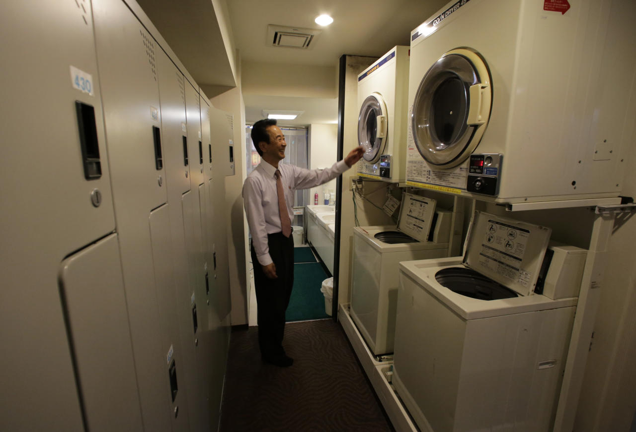 In this Monday, Oct. 29, 2012 photo, manager Akiyoshi Kaneko stands by coin-operated washing machines at the Capsule & Sauna Century Shibuya in Tokyo. The capsule concept has been around for at least 30 years, starting out as lodging for businessmen working or partying late who missed the last train home and needed a cheap place to crash. But budget travelers and other folks curious about a unique lodging experience use them too. (AP Photo/Shizuo Kambayashi)