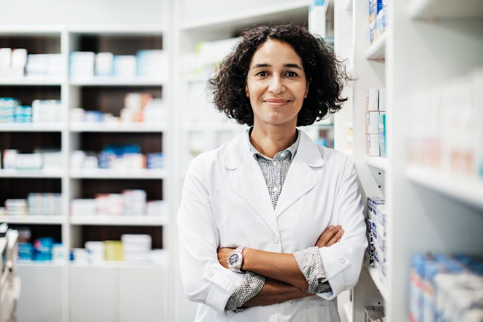 A portrait of a pharmacist standing next some medical supplies in her pharmacy store in the city.