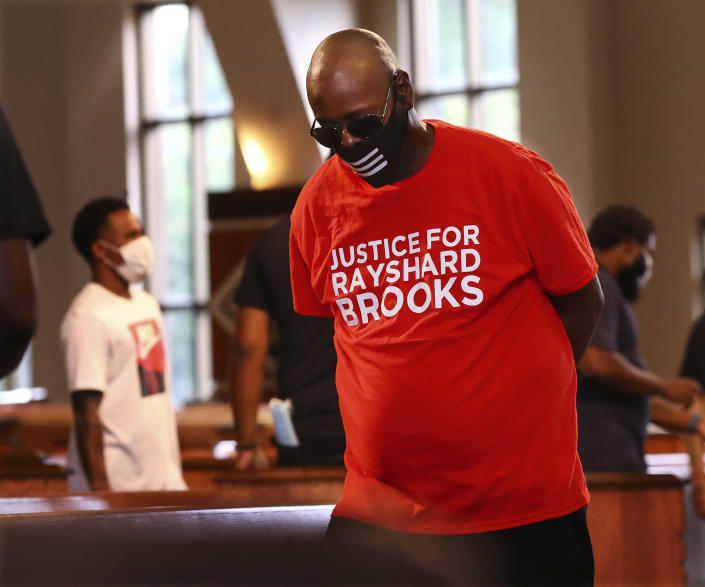 A mourner wears a Justice for Rayshard Brooks shirt while attending a public viewing for Brooks at Ebenezer Baptist Church on Monday, June 22, 2020 in Atlanta. Brooks, 27, died June 12 after being shot by an officer in a Wendy's parking lot. A private funeral for Brooks will be held Tuesday at the church. (Curtis Compton/Atlanta Journal-Constitution via AP, Pool)