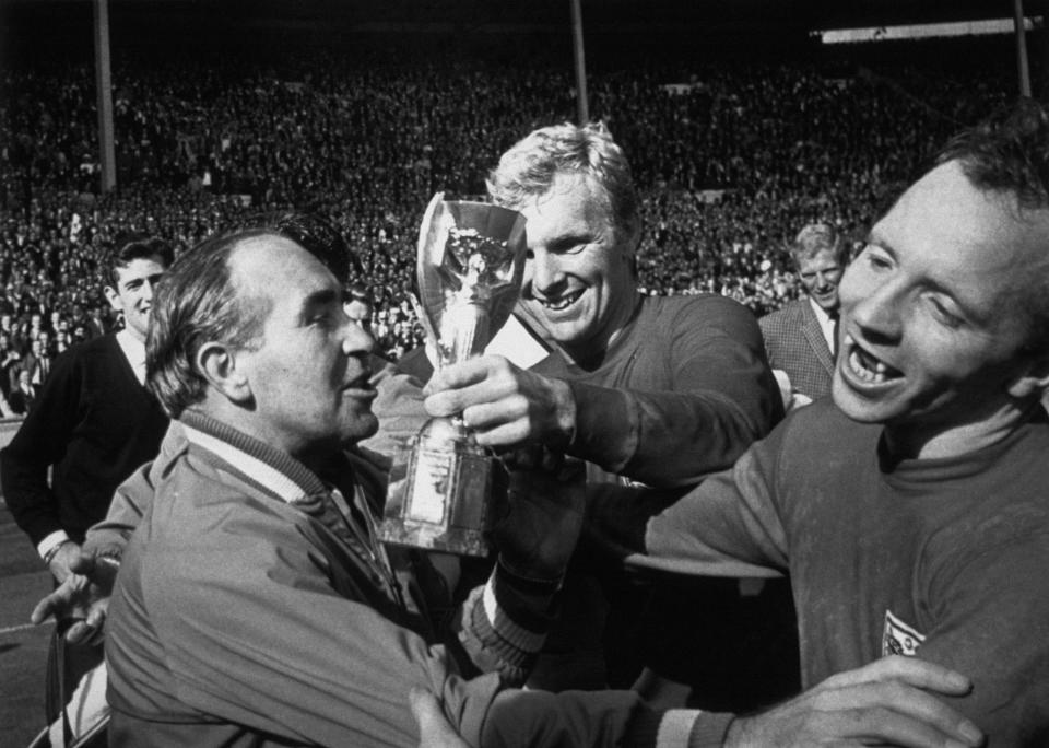 Celebrations following England's win over West Germany in the 1966 World Cup held at Wembley. The England captain, Bobby Moore, holds the Jules Rimmet Cup which the team manager, Alf Ramsay is about to kiss. A delighted Nobby Stiles is also shown. (Photo by Hulton-Deutsch/Hulton-Deutsch Collection/Corbis via Getty Images)
