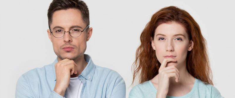Pensive millennial couple stand isolated on grey studio background touch chin with finger thinking of something