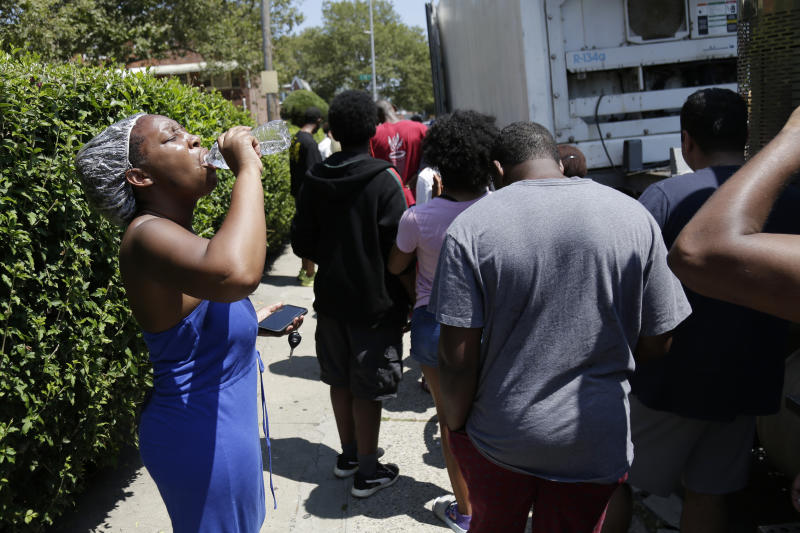 Sharice Allen, left, and others line up to get dry ice from a Con Edison truck in a neighborhood without power in the Brooklyn borough of New York, Monday, July 22, 2019. Mayor Bill de Blasio called for an investigation Monday of power outages that came at the end of this weekend's oppressive heat, saying he no longer trusts utility Con Edison after it decided to turn off power to thousands of customers. (AP Photo/Seth Wenig)