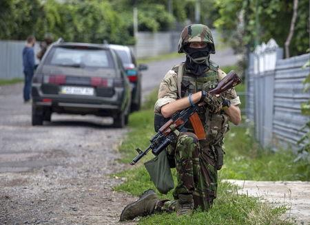A Ukrainian government serviceman takes position while searching for members of Right Sector in the village of Bobovyshche near Mukacheve, Ukraine