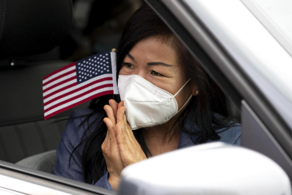 Hathairat Bees Roffers Duangsui, a Thailand native, reacts while holding a small American flag after reciting the citizenship oath during a drive-up naturalization ceremony outside the William J. Nealon Federal Building and United States Courthouse on North Washington Avenue in downtown Scranton, Pa. on Friday, July 17, 2020. (Christopher Dolan/The Times-Tribune via AP)