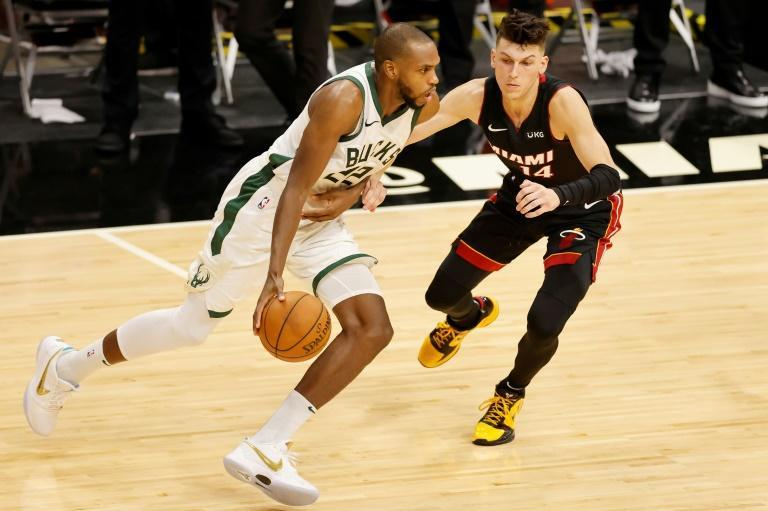 Milwaukee's Khris Middleton (L) drives against Miami's Tyler Herro in the Bucks' 114-97 NBA victory over the Heat
