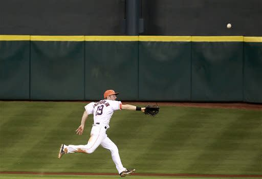 Houston Astros center fielder Robbie Grossman chases down a triple by Detroit Tigers' Andy Dirks during the eighth inning of a baseball game, Saturday, May 4, 2013, in Houston. (AP Photo/Patric Schneider)
