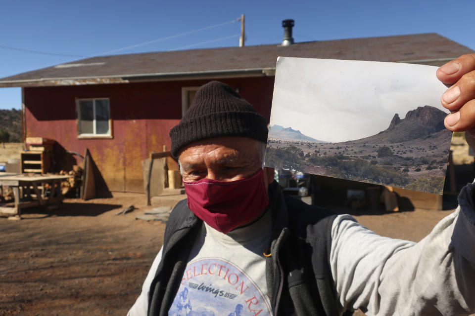 "Raymond Clark displays a photo of a geographic feature known as the ""Praying Mountain"" outside his home in Teesto, Ariz., on the Navajo Nation, on Thursday, Feb. 11, 2021. Teesto workers, health representatives, volunteers and neighbors keep close tabs on another to ensure the most vulnerable citizens get the help they need. (AP Photo/Felicia Fonseca)"