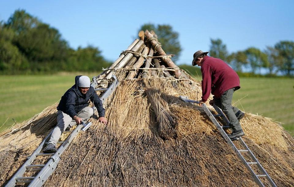 Veteran Jesse Swanson (left) joins Butser Ancient Farm's Will Scanlan as they thatch the roof of a new Bronze Age roundhouse (Andrew Matthews/PA) (PA Wire)