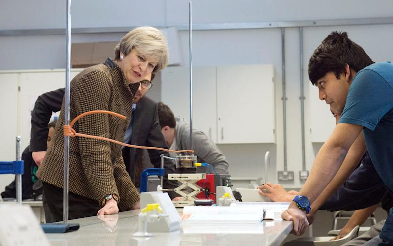 Prime Minister Theresa May observes a physics experiment alongside Head Teacher Dan Abramson with student (on left) Amran Kosmo at King's College London - Credit: Victoria Jones/PA