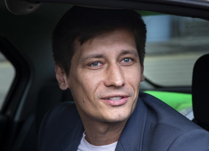 FILE - In this July 30, 2019, file photo, Russian opposition candidate Dmitry Gudkov speaks to journalists sitting inside a police car as he arrives to the court in Moscow, Russia. Gudkov, was briefly arrested in June along with his aunt on fraud charges. Gudkov said he had planned to run in a Moscow district against a less-popular United Russia candidate, but authorities pushed him out of the race. (AP Photo/Alexander Zemlianichenko, File)