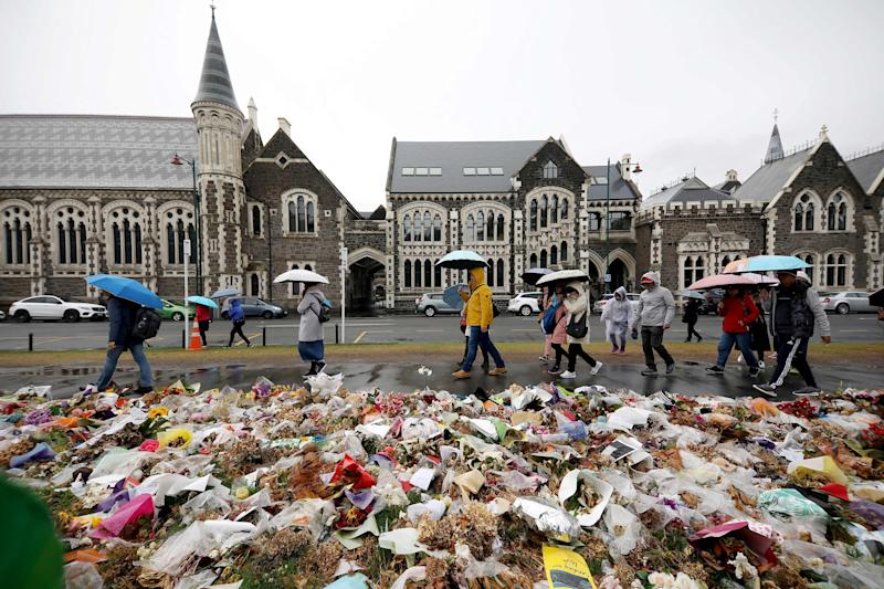 People walk past flowers and tributes displayed in memory of the twin mosque massacre victims outside the Botanical Gardens in Christchurch on April 5, 2019. - The man accused of shooting dead 50 Muslim worshippers in a Christchurch mosque sat impassively April 5 as a New Zealand judge ordered him to undergo tests to determine if he is mentally fit to stand trial for murder. (Photo by Sanka VIDANAGAMA / AFP) (Photo credit should read SANKA VIDANAGAMA/AFP/Getty Images)