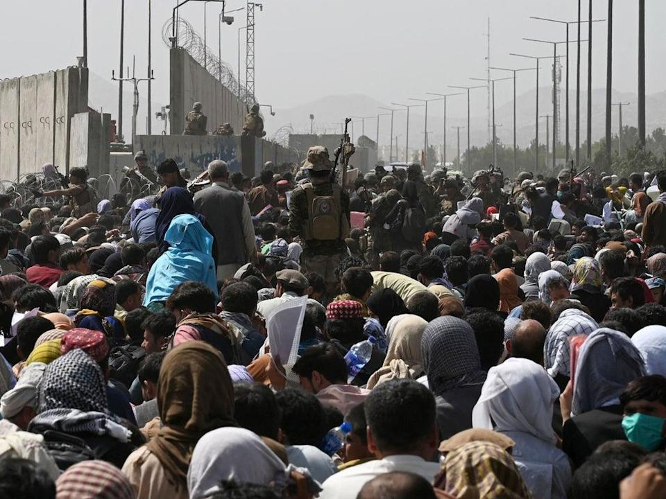Afghans gather on a roadside near the military part of the airport in Kabul in a desperate bid to leave the country  (AFP/Getty)