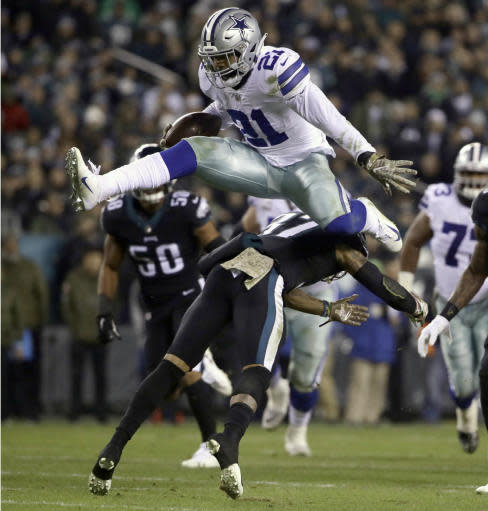 FILE - In this Nov. 11, 2018, file photo, Dallas Cowboys running back Ezekiel Elliott (21) hurdles over Philadelphia Eagles defensive back Tre Sullivan (37) during the first half of an NFL football game, in Philadelphia. Todd Gurley is a big football fan, and Elliott is one of his favorite players. The good feelings are mutual heading into the Cowboys' playoff visit to the Rams and a showdown between the NFL's two premiere running backs. (AP Photo/Matt Rourke, File)