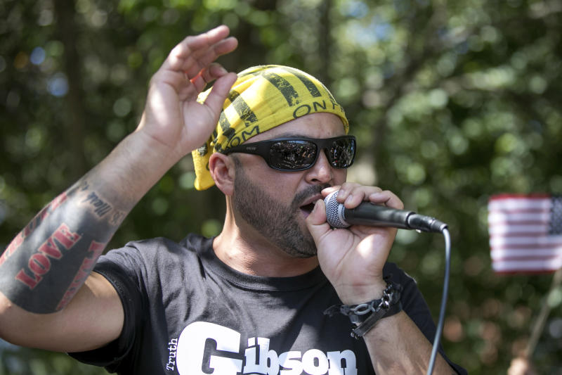 """FILE - In this Aug. 4, 2018 file photo, Patriot Prayer founder and rally organizer Joey Gibson speaks to his followers at a rally in Portland, Ore. On Friday, Aug. 16, 2019 authorities announced they've arrested Gibson, the leader of the right-wing group, on the eve of a far-right rally that's expected to draw people from around the U.S. to Portland on Saturday, Aug. 17, prompting Gibson to urge his followers to """"show up one hundred-fold"""" in response. (AP Photo/John Rudoff, File)"""