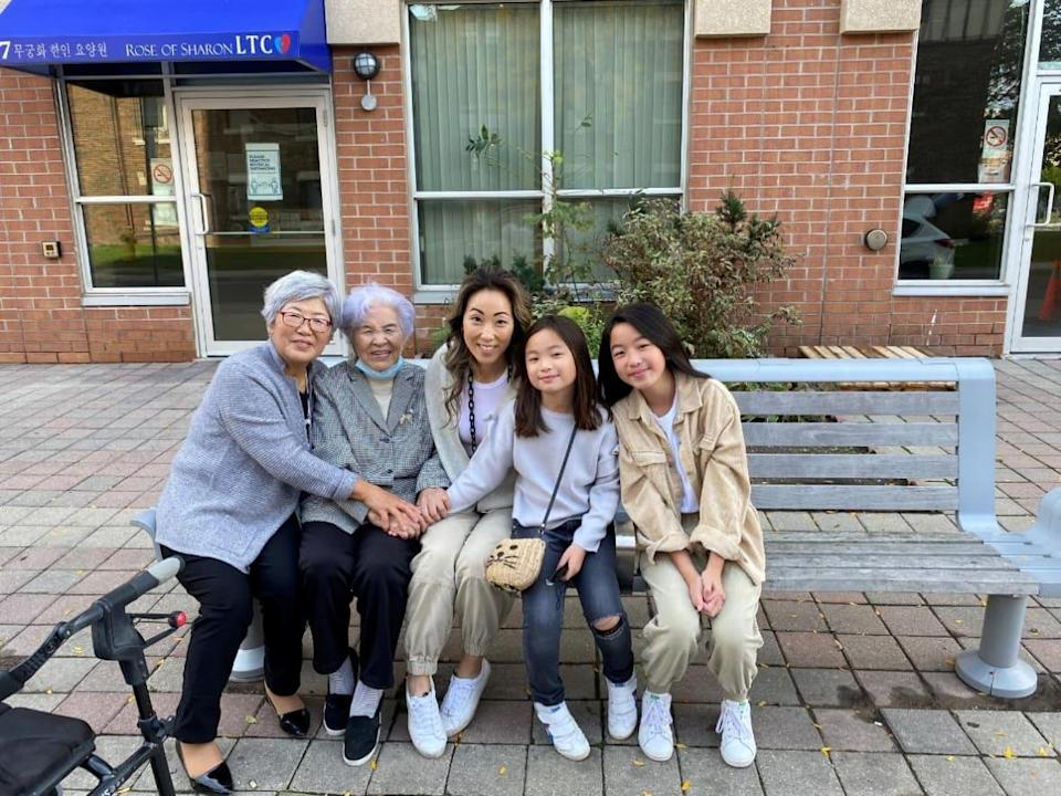 From left to right, Sunja Lee, Bunim Suk, Gina Lee and her two young daughters Lauren and Kate Sy, reunited outside of the Rose of Sharon Korean Long Term Care Home in Toronto on Thanksgiving weekend. (Samantha Lui/CBC - image credit)