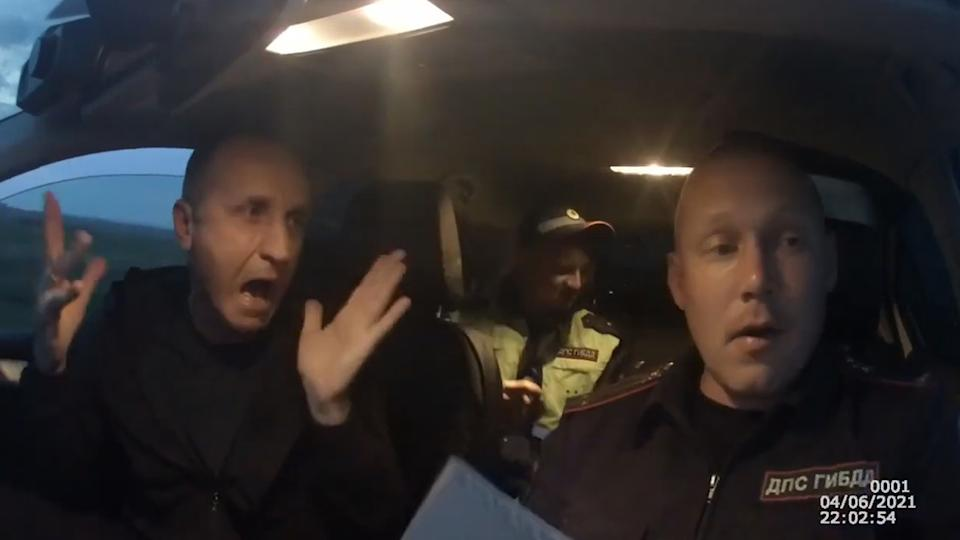 The accused drunk driver gets animated as he speaks to the Russian police officer. Another officer is seen in the back of the patrol car.