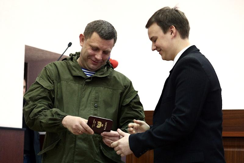 Alexander Zakharchenko (L), leader of the self-proclaimed People's Republic of Donetsk, hands out a new passport in Donetsk on March 16, 2016 (AFP Photo/Aleksey Filippov)