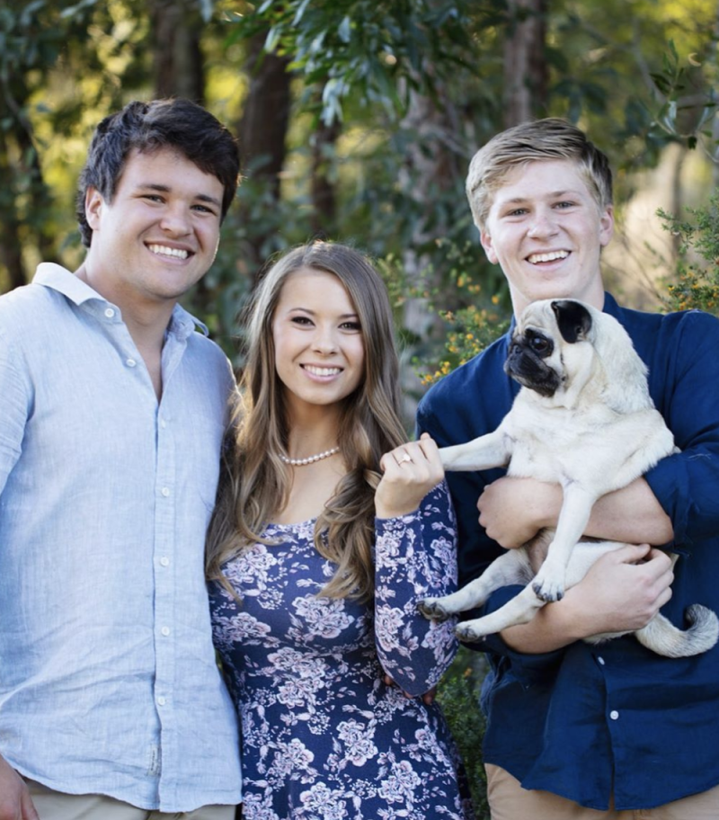 Bindi Irwin, Chandler Powell, Robert Irwin and Stella the pug pose for a photo after Bindi and Chandler's engagement announcement.