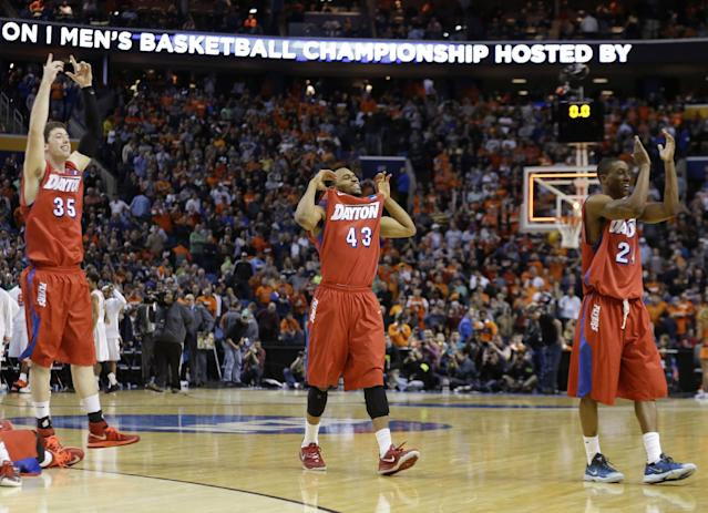 Dayton's Matt Kavanaugh (35), Vee Sanford (43) and Jordan Sibert (24) celebrate during the second half of a third-round game against Syracuse in the NCAA men's college basketball tournament in Buffalo, N.Y., Saturday, March 22, 2014. Dayton won 55-53. (AP Photo/Frank Franklin II)