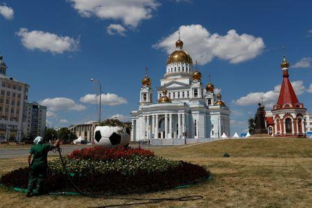 A worker tends a garden with a soccer ball shaped planter next to the Cathedral of St. Theodore Ushakov in downtown Saransk, Russia June 29, 2018. REUTERS/Murad Sezer