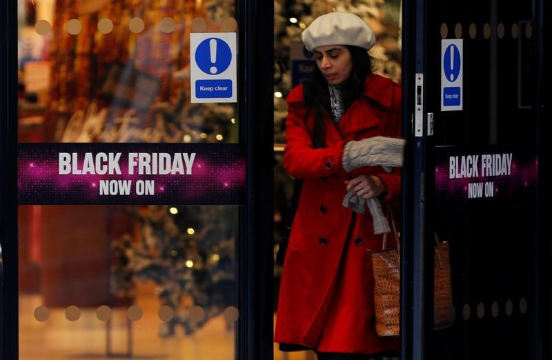 A woman walks past a sign advertising Black Friday offers at a House of Fraser store in Manchester, Britain