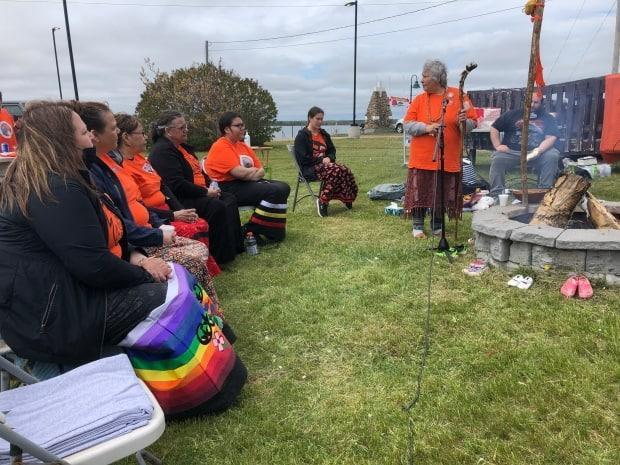 Matilda Snache Knockwood holds the talking stick during the ceremony at Lennox Island on Monday. Orange shirts werethe predominant outfit, in honour of Phyllis JackWebstad, whose grandmother gave her such a shirt to wear to residential school as a young girl. Her teacher confiscated and destroyed it.